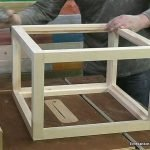 Sanding the wooden display case structure