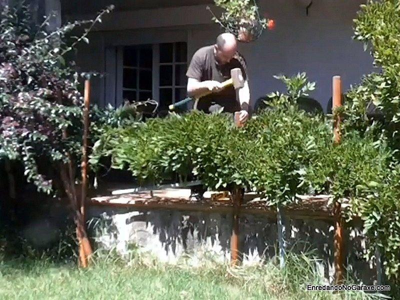 Clavar los postes en el jardín con una maza