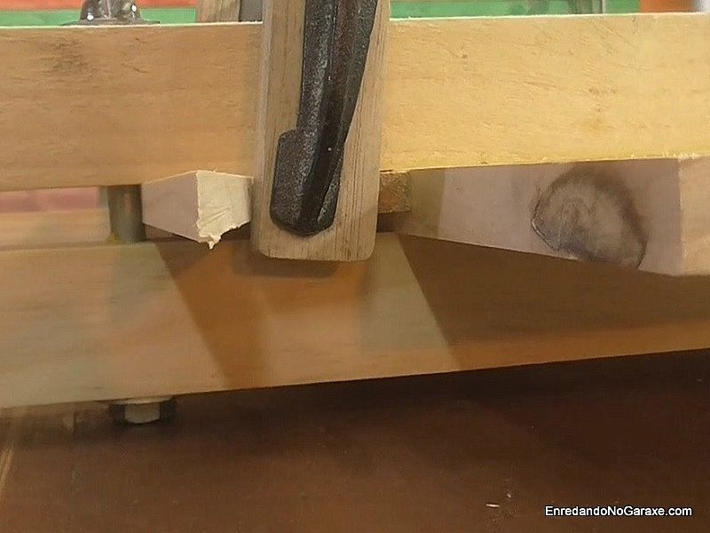 Sargento metálico de carpintero apretando las cuñas de madera