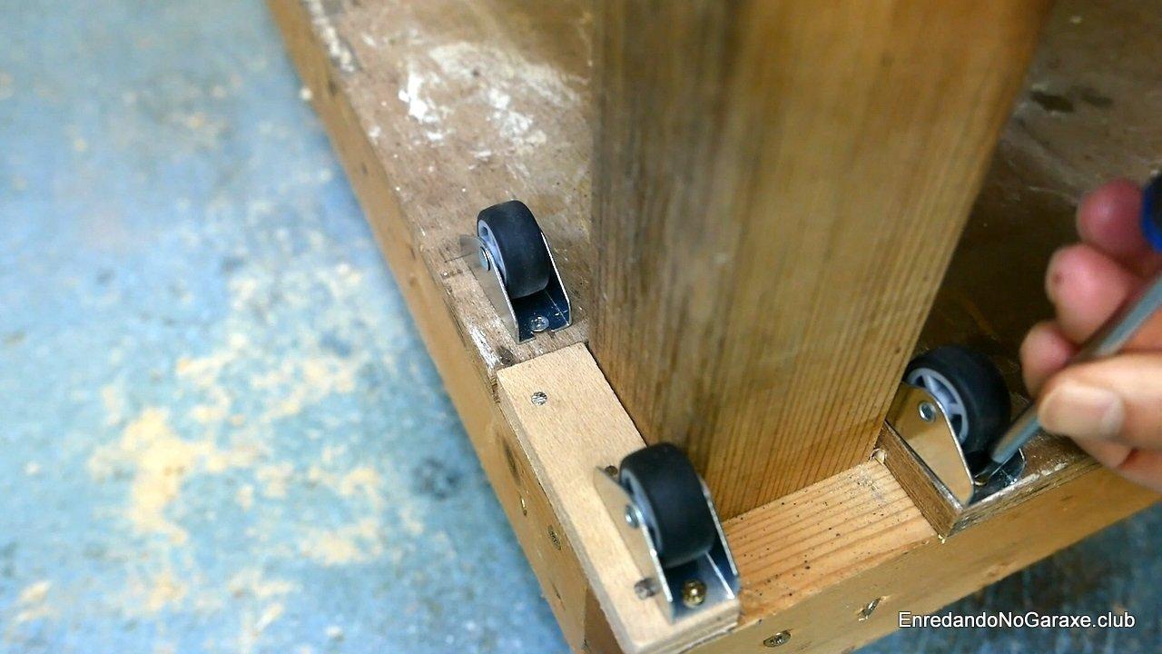 Atornillar ruedas alrededor de la pata del banco de carpintero